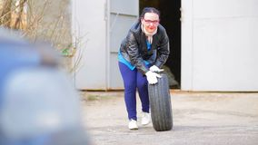 En kvinna i ett läderomslag rullar ut ett bilgummihjul med en diskett ut ur garaget stock video