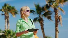 En kvinna i ett ljus - grön skjorta genom att använda minnestavlan mot himlen och palmträden arkivfilmer