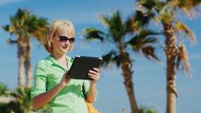 En kvinna i ett ljus - grön skjorta genom att använda minnestavlan mot himlen och palmträden lager videofilmer
