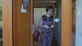 En kvinna i ett prickt-skjorta anseende i dörröppningen lager videofilmer