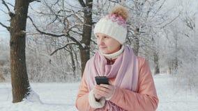 En kvinna i ett rosa omslag tycker om en g? i en vinter parkerar Anv?nder en mobiltelefon lager videofilmer