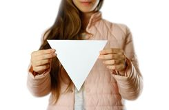 En kvinna i ett varmt vinteromslag rymmer en triangulär vit broschyr blankt papper close upp bakgrund isolerad white royaltyfria bilder