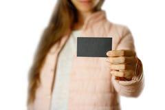 En kvinna i ett varmt vinteromslag som rymmer en svart broschyr blankt papper close upp bakgrund isolerad white fotografering för bildbyråer