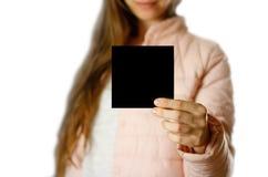 En kvinna i ett varmt vinteromslag som rymmer en svart broschyr blankt papper close upp bakgrund isolerad white royaltyfria bilder