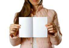 En kvinna i ett varmt vinteromslag som rymmer en vit broschyr blankt papper close upp bakgrund isolerad white arkivfoto