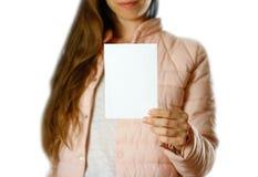 En kvinna i ett varmt vinteromslag som rymmer en vit broschyr blankt papper close upp bakgrund isolerad white royaltyfri fotografi
