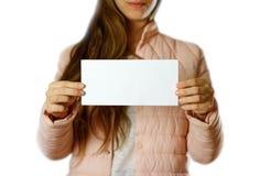 En kvinna i ett varmt vinteromslag som rymmer en vit broschyr blankt papper close upp bakgrund isolerad white arkivbilder