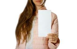 En kvinna i ett varmt vinteromslag som rymmer en vit broschyr blankt papper close upp bakgrund isolerad white royaltyfria foton