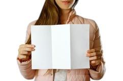 En kvinna i ett varmt vinteromslag som rymmer en vit broschyr blankt papper close upp bakgrund isolerad white arkivbild