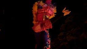 En kvinna i en färgrik dräkt och en mystisk maskering dansar, hänryckt, inte lägereld lager videofilmer