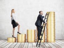 En kvinna i formell kläder går upp att använda trappa som göras av guld- mynt, medan en man har funnit en genväg hur man når Arkivbild