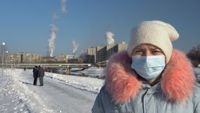 En kvinna i en framsidamaskering mot bakgrunden av att röka rör i en vinter stock video