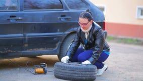 En kvinna i handskar pumpar ett bilgummihjul med en kompressor arkivfilmer