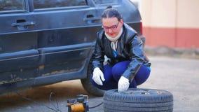 En kvinna i handskar pumpar ett bilgummihjul med en kompressor stock video