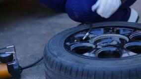 En kvinna i handskar pumpar ett bilgummihjul med en kompressor lager videofilmer