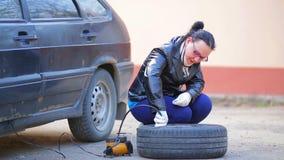 En kvinna i handskar sätter in en kompressortråd för att pumpa in i ett bilgummihjul på en diskett stock video