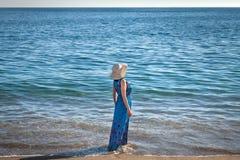 En kvinna i hatten på stranden royaltyfri fotografi