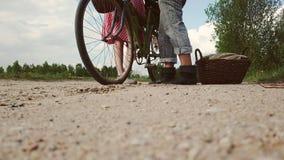 En kvinna i en klänning med en cykel kommer till en man stock video