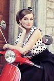 En kvinna i makeup på en röd retro sparkcykel fotografering för bildbyråer