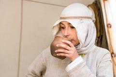 En kvinna i en medeltida klänning dricker från en leramaträtt arkivbild