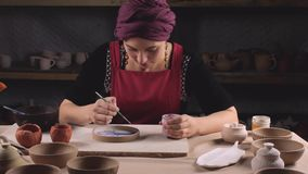 En kvinna i nationell klänning målar en platta av målarfärg Seminariumproduktion av keramisk bordsservisproduktm?lning stock video