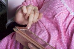 En kvinna i en nattlinne arbetar med en minnestavla, medan ligga i säng Hon trycker på skärmen med henne fingrar Royaltyfri Bild