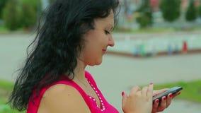 En kvinna i en röd klänning är i parkera och skriver ett meddelande i hennes telefon arkivfilmer