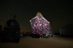 En kvinna i en siden- klänning ser stjärnklar himmel i en tältplats i mitt av den ergChebbi öknen arkivbild