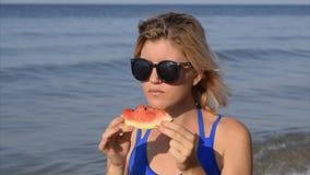 En kvinna i solglasögon äter ett vattenmelonsammanträde på stranden En mogen vattenmelon i händerna av en blondin lager videofilmer