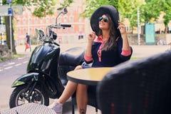En kvinna i solglasögon och solig hatt sitter på tabellen i ett streetrkafé royaltyfria foton