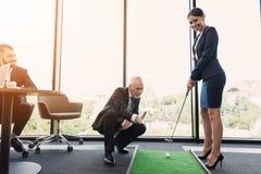 En kvinna i en svart affärsdräkt spelar golf i kontoret En gamal man i en affärsdräkt hjälper henne Royaltyfri Foto