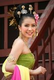 En kvinna i THAILÄNDSK RETRO KLÄNNING poserar för ett fotografi arkivfoto