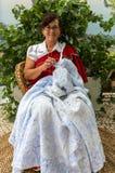 En kvinna i en traditionell klänning broderar en borddukdurnig madeiravinfestivalen i Funchal madeira portugal Arkivfoton