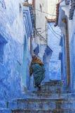 En kvinna i typiska moroccan kläder, blåa Medina av Chefchaouen Royaltyfria Bilder