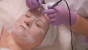 En kvinna i en vit maskering är i ett medicinskt kontor Händerna av en kosmetolog i släta skrynklor för handskar med hjälpen av e arkivfoto