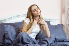 En kvinna känner en öm hals Hon har en f?rkylning Hon vaknade upp i morgonen och fick sjuk arkivfoton