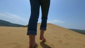 En kvinna kör längs sanden i öknen En flicka kör barfota på en sanddyn i sanden arkivfilmer