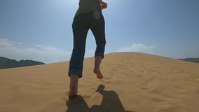 En kvinna kör längs sanden i öknen En flicka kör barfota på en sanddyn i sanden stock video