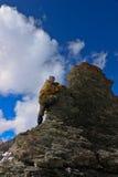 En kvinna klättrar en klippa. Fotografering för Bildbyråer