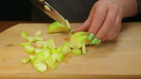 En kvinna klipper ett gr?nt ?pple med en kniv p? ett tr?br?de in i sm? kuber lager videofilmer