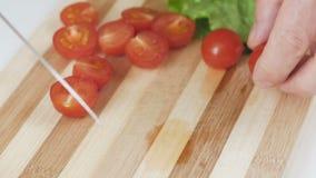 En kvinna klipper en körsbärsröd tomat med en kniv på ett delat bräde arkivfilmer
