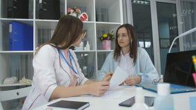 En kvinna kom till mottagandet till doktorn Konversationen av doktorn och patienten arkivfilmer