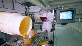 En kvinna kontrollerar arbete av den automatiserade transportören, rörande chiper in i en behållare lager videofilmer