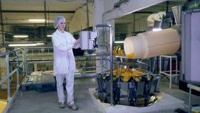 En kvinna kontrollerar arbete av fabrikstransportören, rörande potatischiper stock video
