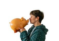 En kvinna kysser en spargris royaltyfri fotografi