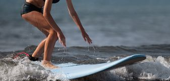 En kvinna lär att surfa på vågen arkivbilder