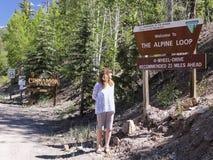 En kvinna läser ett alpint tecken för den öglasBackcountry bywayen Arkivfoto
