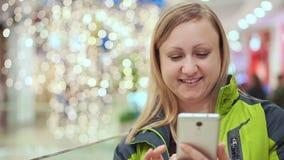 En kvinna läser ett smartphonemeddelande, och le, står hon i en köpcentrum, mot en bakgrund av a stock video