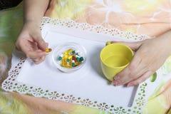 En kvinna ligger i säng under en filt under sjukdom Ta en minnestavla med ett magasin för behandling och ett exponeringsglas av v Royaltyfri Foto