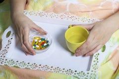 En kvinna ligger i säng under en filt under sjukdom Tar ett magasin med ett magasin för behandling och ett exponeringsglas av vat Arkivbild